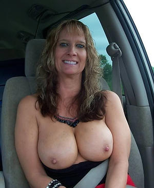 Lovely nude mature in car